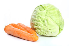 The big  fresh heads of cabbage and carrots. The big  fresh heads of cabbage  and  three carrots on table Stock Image