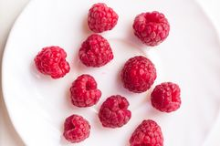 Raspberries on a white saucer close up. Big fresh juicy raspberries on a white saucer close up, selected focus Stock Image