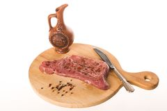 Big fresh steak on wooden plate with pepper, knife and jug royalty free stock photo