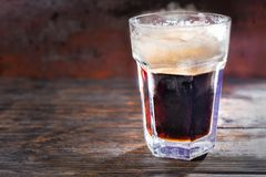 Big frozen glass with freshly poured dark beer and head of foam. On wooden desk. Food and beverages concept Stock Photos