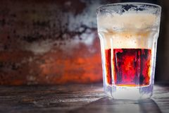 Big frozen glass with freshly poured red beer and head of foam o. N dark wooden desk. Food and beverages concept Stock Photos