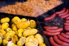 Catering food, sausages with potatoes and stewed cabbage. Big frying pan with sausages, potatoes and stewed cabbage, catering food outdoors stock photography