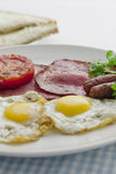 Big and full breakfast. Sunny-side up with ham and tomato with  bread on the side in white background Royalty Free Stock Photography