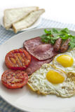 Big and full breakfast. Sunny-side up with ham and tomato with baked bean on the side Royalty Free Stock Photos