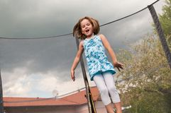 Big fun - child jumping trampoline stock image