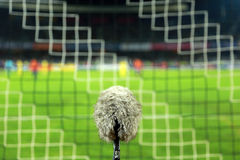 Big and furry sport microphone on a soccer field behind the goal Royalty Free Stock Images