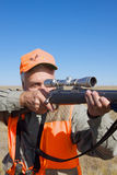 Big Game Hunter. A big game hunter with rifle up looking through his scope Royalty Free Stock Image