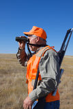 Big Game Hunter Glassing. A big game hunter with rifle glassing for game Stock Photography