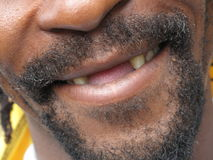 Big gap. Close up of an african american male mouth with a big open smile and the traditional gap surrounded by a beard Royalty Free Stock Photos