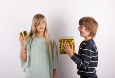 Big gift and small gift - siblings with with present boxes in di Stock Photo