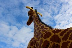 A Big Giraffe builded from plastic bricks. A lot of pieces of plastic bricks in brown and yellow colors stock photos