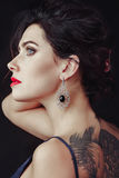 Big girl and Sapphire. A beautiful, elegant ,yet stylish woman, with pure blue eyes and a bold tattoo wearing a luxurious large sapphire earrings, looking away Royalty Free Stock Photos