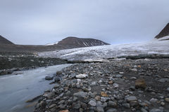 Big glacier in between mountain valley and river flowing fast with melted ice, Sarek, Sweden Royalty Free Stock Photo