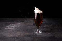A big glass of beer full with brown ale and with white foam blowed away on a dark stone background. Royalty Free Stock Images