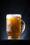 Big glass of beer over a dark background stock images