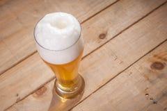 Big glass of beer on wood Stock Image