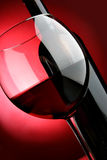 Big glass and bottle of red wine. Over red background Stock Images