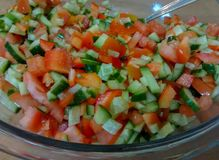 Big glass bowl with cucumber and tomato vegetable salad. In this picture there is a big glass bowl filled with vegetable salad, made of cucumbers and tomatoes royalty free stock photo