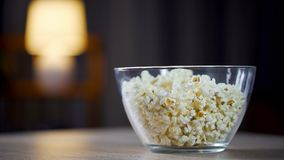 Big glass bowl of salty popcorn standing on table, treatment for home party. Stock footage Stock Image
