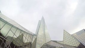Big glass building dirty window panes. This is footage of a big triangle or pyramidal building surround by glass and mountains and a gray sky, very cool stock video