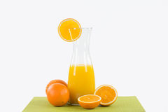 Big glass carafe with orange juice on a green table runner, deco Royalty Free Stock Photos