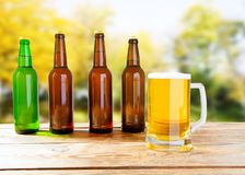 Big glass cup of beer on old wooden table on blurred park background royalty free stock images
