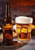 Big glass with freshly poured beer and head of foam near bottle. And plates with snacks on dark wooden desk. Food and beverages concept Stock Photography