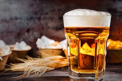Big glass with freshly poured beer and head of foam near plates. With snacks on dark wooden desk. Food and beverages concept Royalty Free Stock Photos