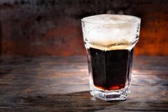 Big glass with freshly poured dark beer and head of foam on wood. En desk. Food and beverages concept Stock Images