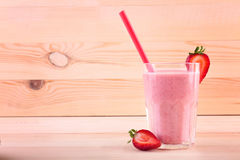 A big glass full of appetizing smoothie. A berry shake on a wooden background. Tasty milkshake with a straw and cut strawberries. Stock Images