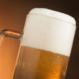 Big glass with handle filled with fresh beer with a lot of foam Stock Photography