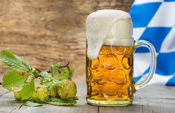 Big glass of lager beer in Bavaria at Oktoberfest in Munich. With Bavarian flag in background stock image