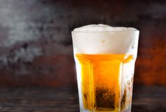 Big glass with a light beer and a head of foam on old dark desk. Drink and beverages concept Stock Image
