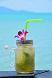 Big glass of mojito with orchid flower on beach Royalty Free Stock Photography