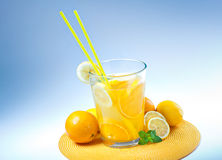 Big Glass of orange and lemon juice on blue Stock Photo