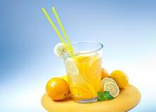 Big Glass of orange and lemon juice on blue. Background Stock Photo