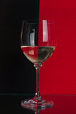 Big glass on red and black. The photo shows the glass of wine on the background of two colors Royalty Free Stock Images