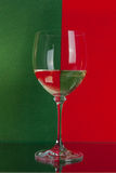 Big glass on red and green. The photo shows the glass of wine on the background of two colors Stock Photography