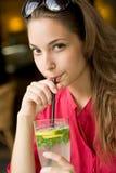 Big glass of refreshment. Big glass of refreshment, beautiful young brunette woman drinking lemonade royalty free stock photography