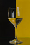 Big glass on yellow and black. The photo shows the glass of wine on the background of two colors Royalty Free Stock Photo