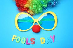 Big glasses, clown nose and rainbow wig. On color background. April fool`s day celebration Royalty Free Stock Photo