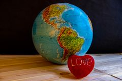 Big globe on a black background with the image of the American continents and with a red heart with the word `love`. royalty free stock images