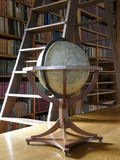 Big globe in the library. A big globe near the library window, trestle ladder and rows of books on shelves in the background Stock Images
