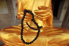Big gold budda with beads in his hand Royalty Free Stock Photos