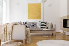 Big gold painting on wall. Big gold painting on white wall in unique living room with fireplace and white carpet Royalty Free Stock Photography