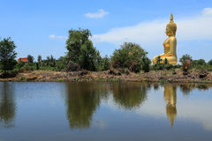 Big  golden buddha statue sitting reflection on the water. With blue sky background Royalty Free Stock Images