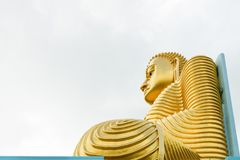 Big golden Buddha statue in wheel-turning pose. Big golden Buddha statue in sitting pose on the top of a building with cloudy white sky on background Royalty Free Stock Images