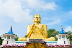 Big golden Buddha statue in wheel-turning pose in Dambulla Golde. Big golden Buddha statue in wheel-turning pose on the top of Golden cave temple in Dambulla Royalty Free Stock Image