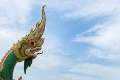 Big golden Naga statue with blue and white sky background. The serpent deity in Buddhist `Naga` golden head with blue and white sky showing what Thai people Stock Photography