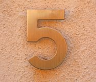 Big golden number 5. Golden number 5 on the wall of a house stock photography